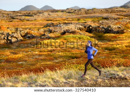 Woman trail runner running in mountain landscape. Female runner in warm winter and fall outfit jogging cross country outdoors in beautiful nature. - stock photo