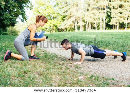 Woman trainer motivates men to do push-ups - stock photo