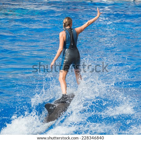 Woman-trainer riding on dolphin in water pool.