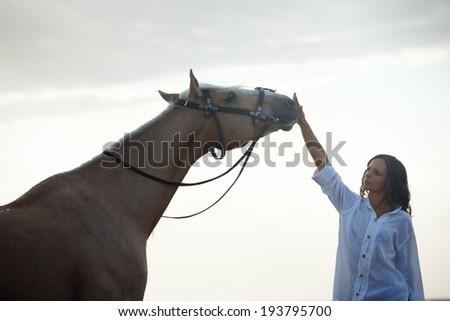 Woman training horse outdoors during sunrise - stock photo