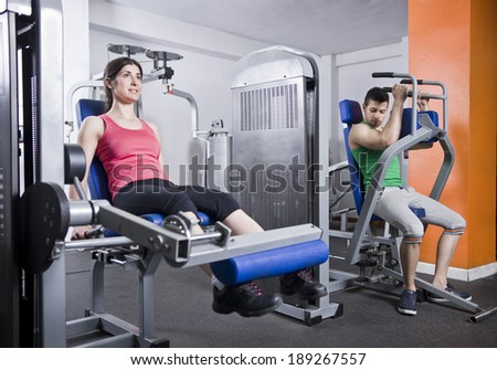 Woman training legs in gym and man training pectoral muscle in background