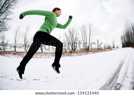 Woman training running in winter on snow. Copy space. Health and fitness concept. - stock photo