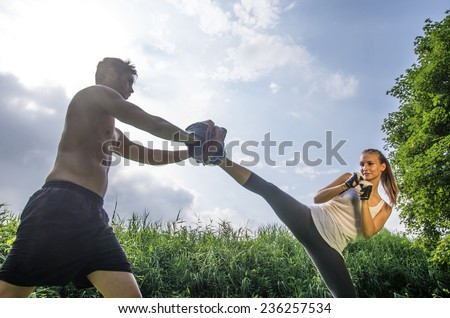 Woman training  self defense martial arts with coach - Martial arts athlete kicks  - stock photo