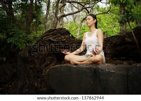 Woman training yoga and meditation on the rock at the mountain - stock photo