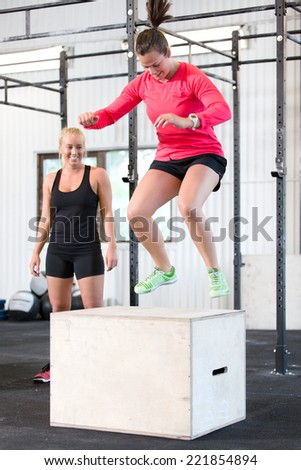 Woman trains box jumps with her team - stock photo