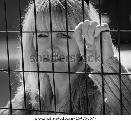Woman trapped on outside of metal fence looking inside
