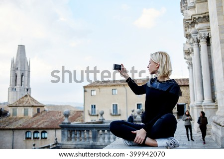 Woman traveler is making photo with mobile phone camera of a old tower,while she is relaxing in the fresh air after excursion in museum. Female tourist is shooting video of city view on cell telephone - stock photo