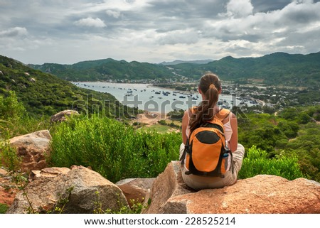 Woman traveler looks at the edge of the cliff on the  sea bay of mountains in the background - stock photo