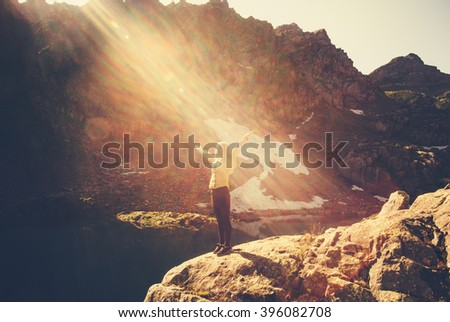 Woman Traveler meditating yoga relaxing alone standing on cliff sun light Travel healthy Lifestyle concept lake and rocky mountains landscape on background outdoor  - stock photo