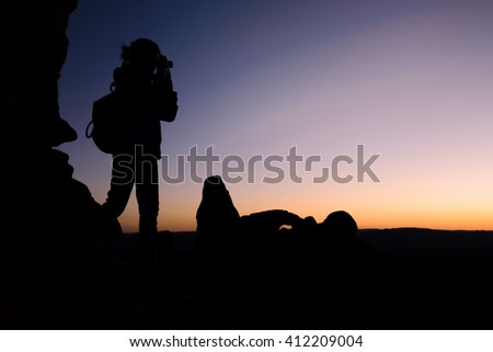 Woman traveler shooting picture at sunset, silhouette. Outdoor activity - stock photo