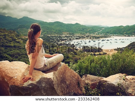 Woman traveler sits and looks  at the edge of the cliff on the sea bay - stock photo