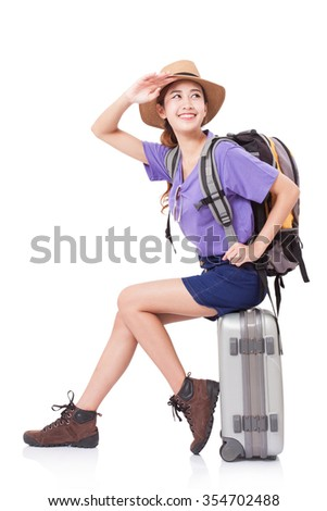 Woman traveler sitting on suitcase with backpack on white background - stock photo