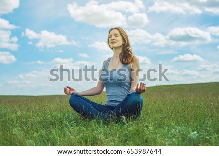 Woman traveler sitting on the meadow with green grass under blue sky with clouds in the Lotus position. Meditating in complete tranquility and freedom