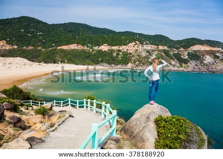 Woman traveler standing on the rock with great sea view - stock photo
