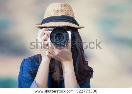 woman traveler wearing blue dress as photographer, take photo with camera outdoor - stock photo