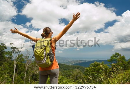 Woman traveler with backpack enjoying mountains view with raised hands .Traveling along Asia, freedom and active lifestyle concept - stock photo