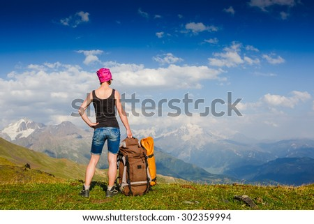 Woman Traveler with Backpack enjoying the mountain view - stock photo