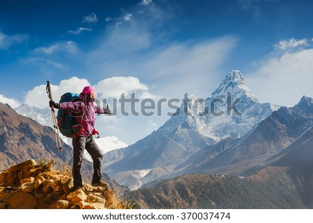 Woman Traveler with Backpack enjoying the mountains in Himalayas  - stock photo