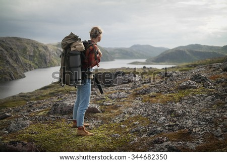 Woman Traveler with Backpack hiking in Mountains. - stock photo