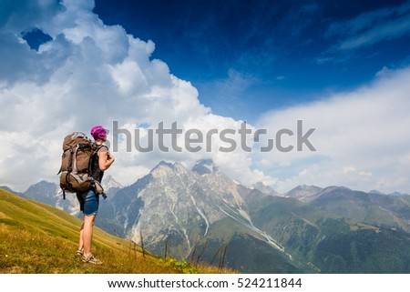 Woman Traveler with Backpack hiking in the Mountains with beautiful summer landscape