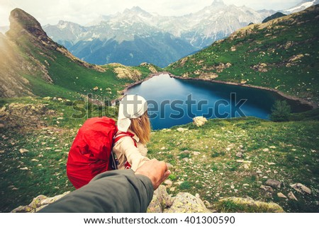 Woman Traveler with backpack holding Man hand following Travel hiking Lifestyle and relationship concept lake and mountains landscape on background - stock photo