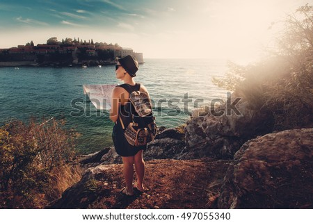 Woman traveler with map near sea at sunset