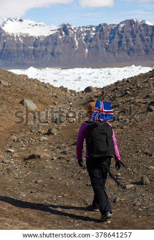 Woman traveller exploring around Jokulsarlon glacier Lagoon with iceland flag flying in the wind