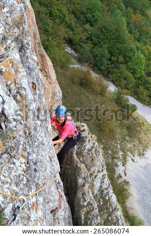 Woman traversing along steep rock face while climbing high above the ground - stock photo