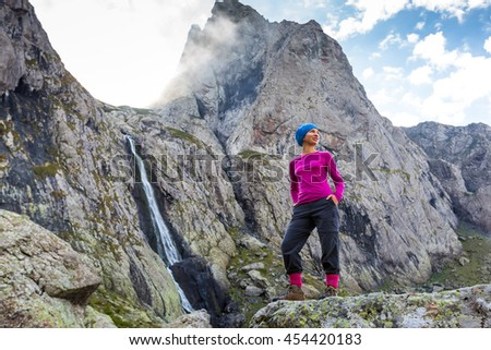 Woman trekker is standing against high mountains waterfall in Caucasus, Georgia