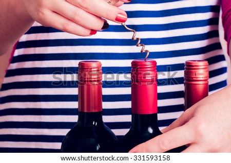 Woman tries open a bottle of wine with a corkscrew - stock photo