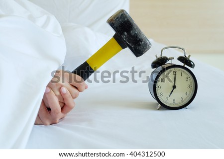woman tries to break the alarm clock with hammer - stock photo