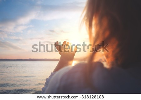 woman try to grab the sun - stock photo