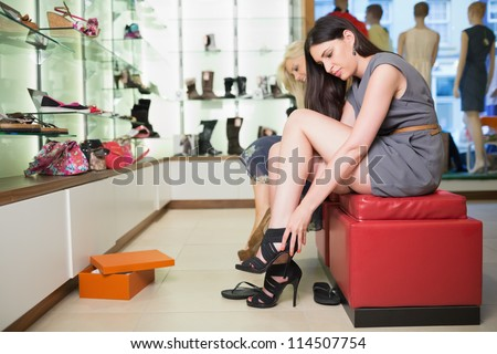 Woman trying black shoes sitting in a shop - stock photo