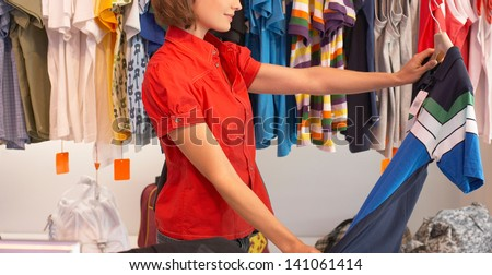 Woman trying dress, shopping for clothing - stock photo