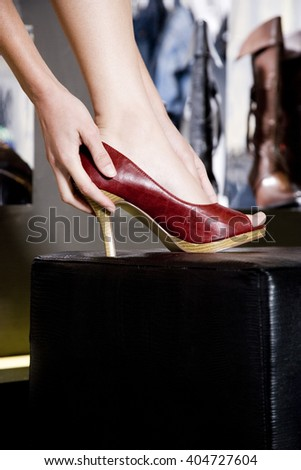 Woman trying on high-heeled shoes in a shoe shop, close-up of foot - stock photo