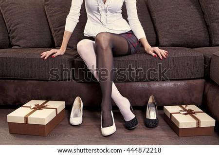 woman trying on several pairs of new shoes in the mall - stock photo