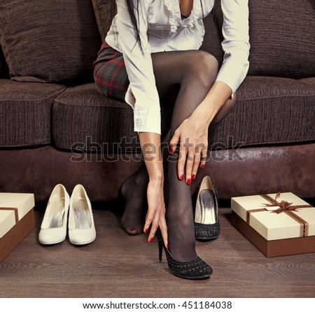 woman trying on several pairs of shoes in the mall - stock photo