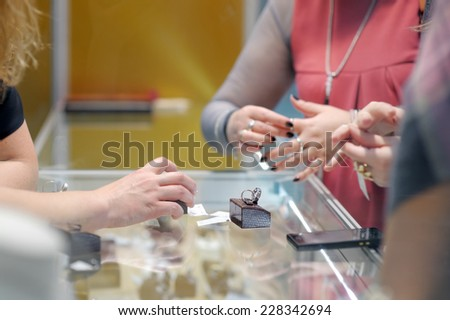Woman trying rings at a jeweler - stock photo