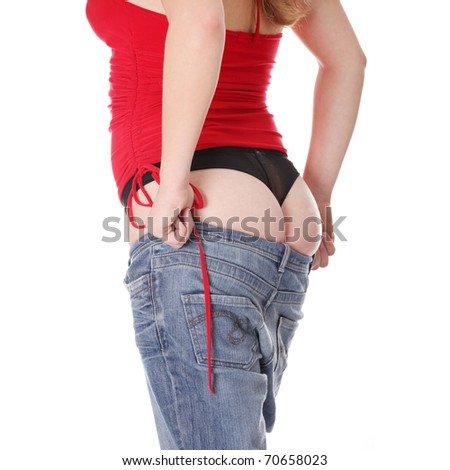 Woman trying to get in to old jeans. Isolated on white - stock photo