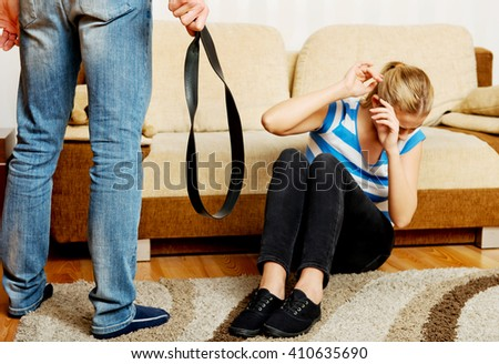 Woman trying to hide herself while man standing with belt in hand - stock photo