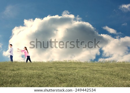 Woman trying to hug man against cloudy sky - stock photo