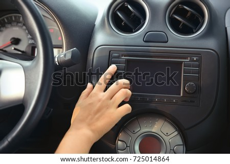Woman tuning radio in car