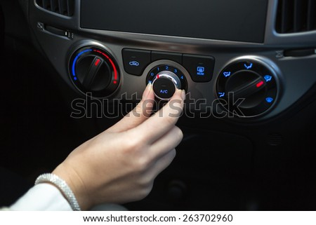 Woman turning on car air conditioning system - stock photo