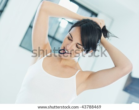 woman tying hair with rubber band in mouth - stock photo