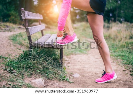 Woman tying shoelaces before start running - Sportive girl jogging in a park , close up on running shoes - Concepts about sport and lifestyle