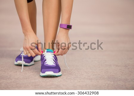 Woman tying sports shoe - stock photo