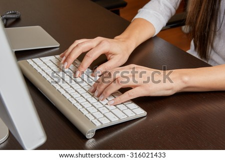 Woman typing on a computer keyboard on a wooden desk in front of a screen in the office.
