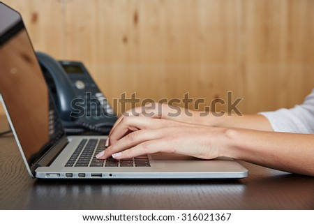 Woman typing on a laptop computer on a wooden desk in the office
