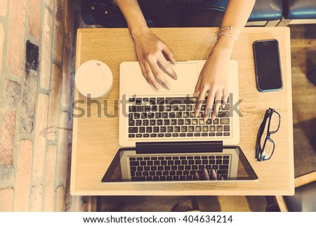 Woman typing on computer keyboard in a cafe. The table is small and there are a phone, a cup and eyeglasses on it. Hands are the only part visible of the young woman. High up view.