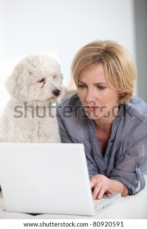 Woman typing on laptop computer next to small white dog